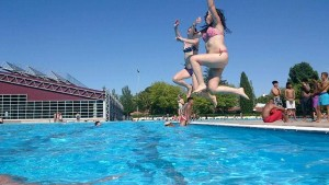 Madrid beaches: young ladies jumping into the water in an outdoor pool